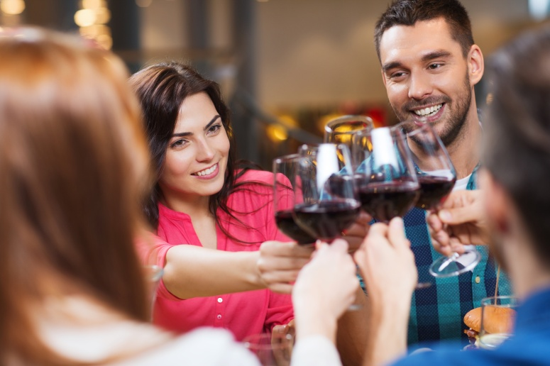 friends clinking glasses of wine at restaurant